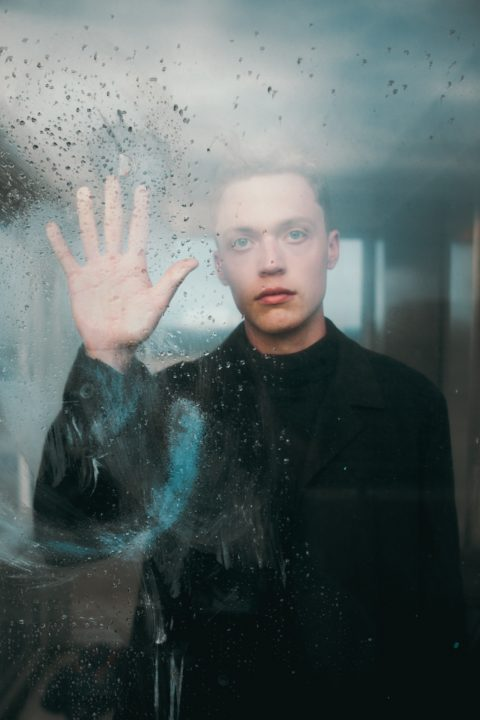 Smutny nastolatek trzyma rękę na szybie i patrzy przed siebie